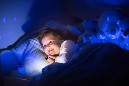 petite fille dans lit et ciel étoilé